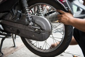 man performing a change of a motorcycle tire
